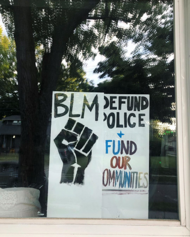 Window sign says BLM, Defund Police + Fund Our Communities