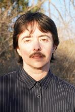 Head shot of a white man with brown hair and mustache, standing outside. He is wearing a black and white button-up shirt.