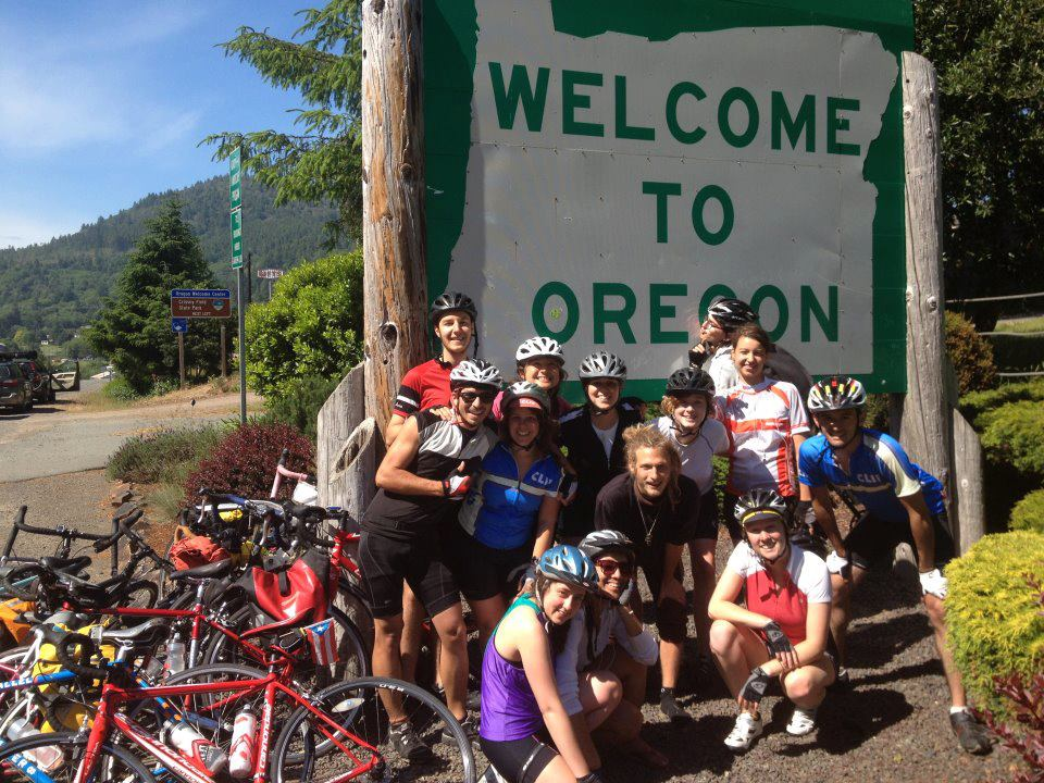 "Co-cycle members on bikes, standing next to ""Welcome to Oregon Sign"""